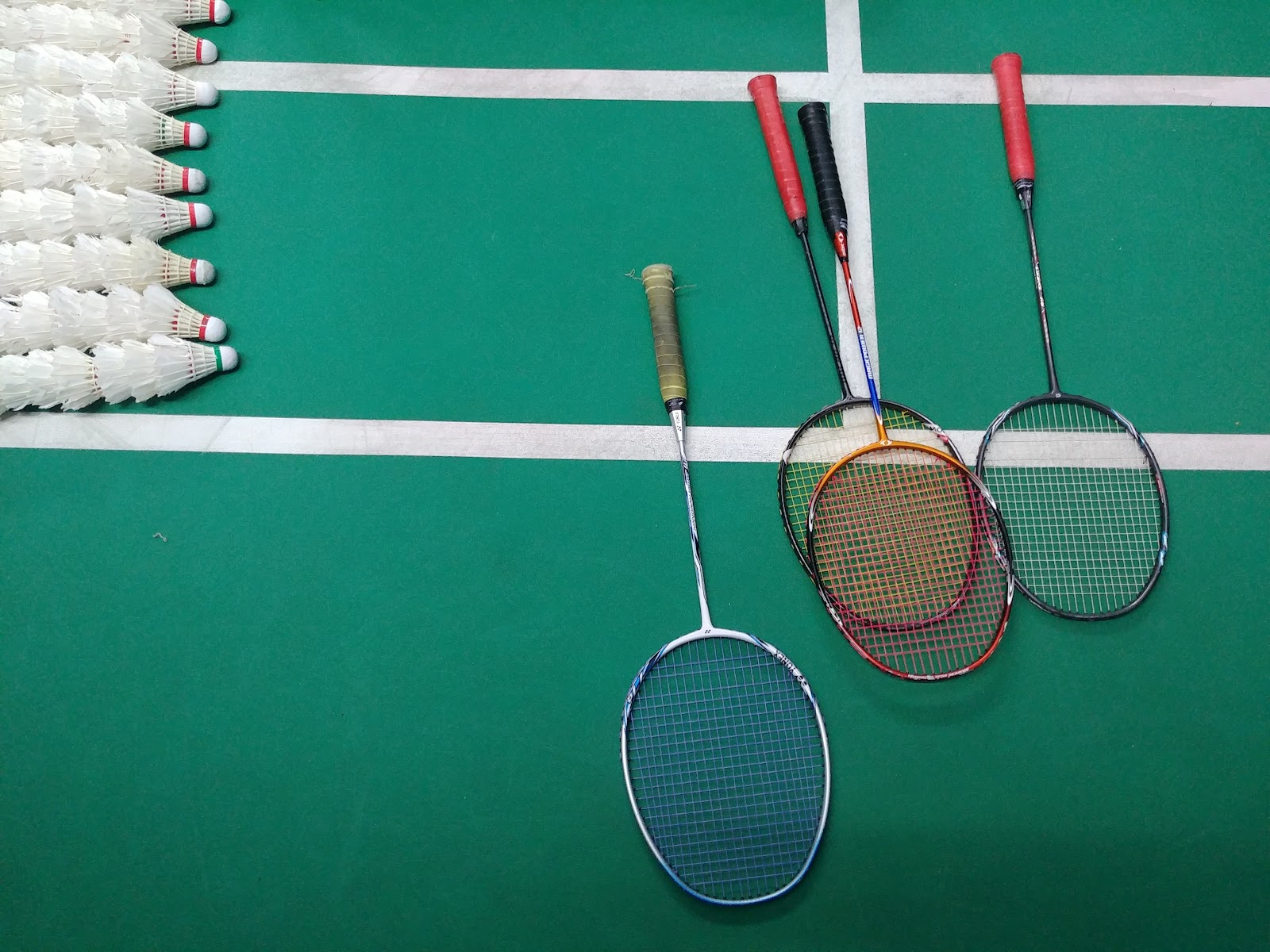 This is a shot of dozens of shuttlecocks and several badminton rackets laying on a green surfaced badminton court.