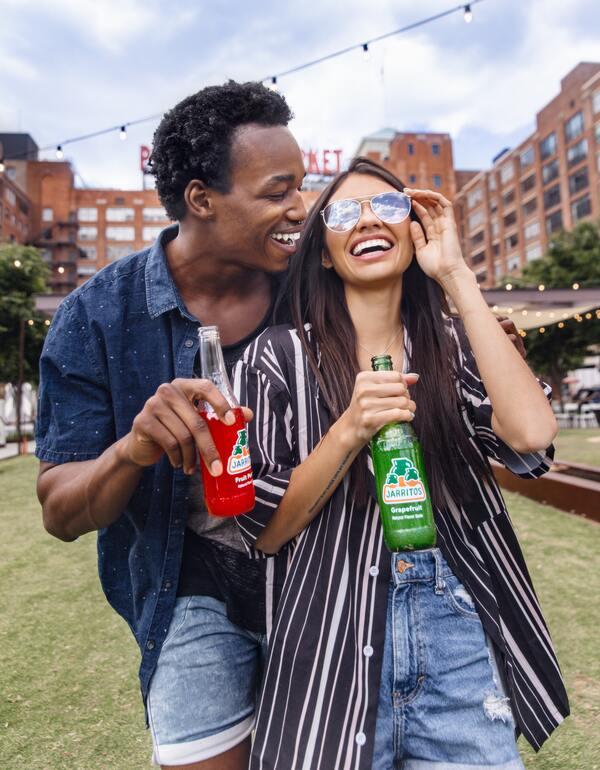 Dois amigos rindo e bebendo Jarritos, um refrigerante