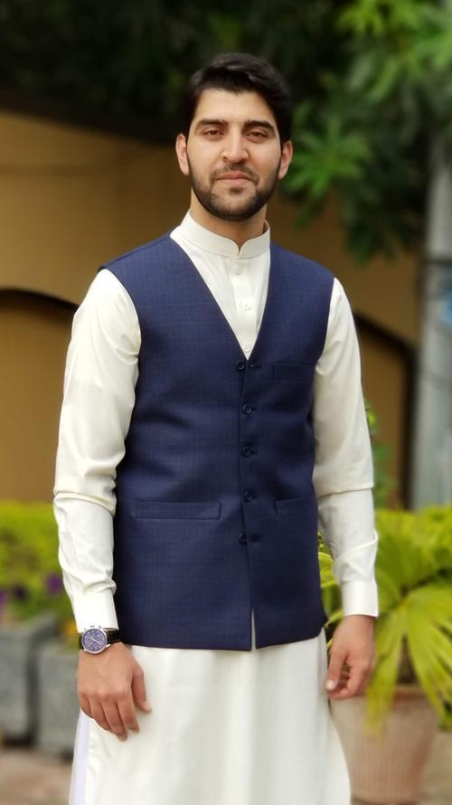 Amin Khan smiling at the camera. He is wearing a white dress shirt with a blue vest.