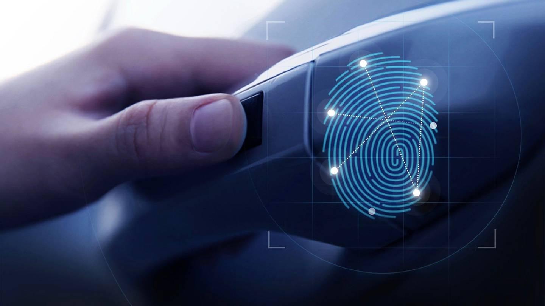pressing hand on fingerprint sensor on car door handle