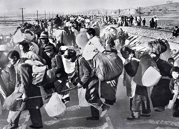 Refugees carrying their belongings on their backs after the North Korean invasion.