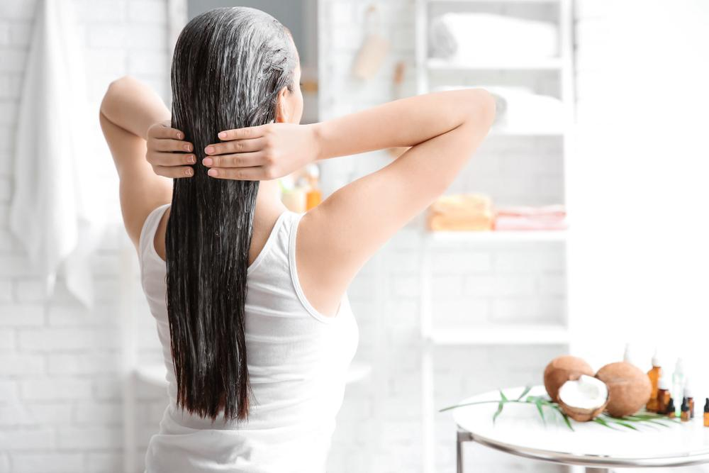 A person holding her hair  Description automatically generated with low confidence
