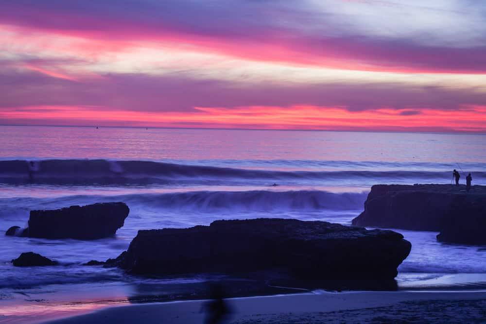 A pink and purple sunset in Santa Cruz over the ocean with waves coming in