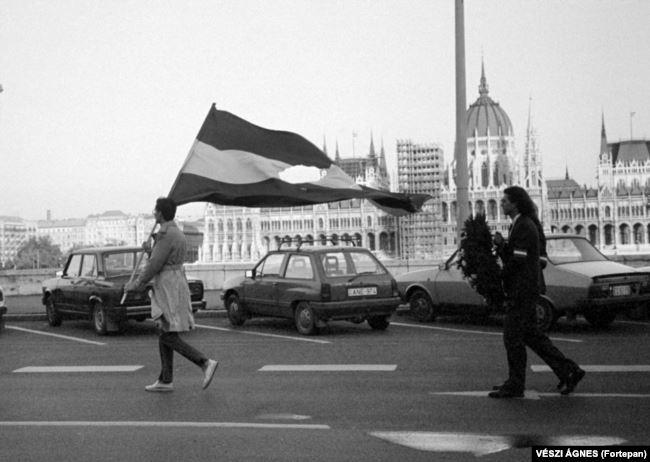 Человек с национальным флагом Венгрии. В центре вырезан социалистический герб (звезда, колосья, молот и т. д.). Фотография 1990 года, но точно так же вырезали коммунистическую символику с флага в 1956 году. В 1990 году в Венгрии прошли первые за почти пять десятилетий свободные выборы. Советские войска уже начали покидать страну. Их вывод официально завершился 19 июня 1991 года