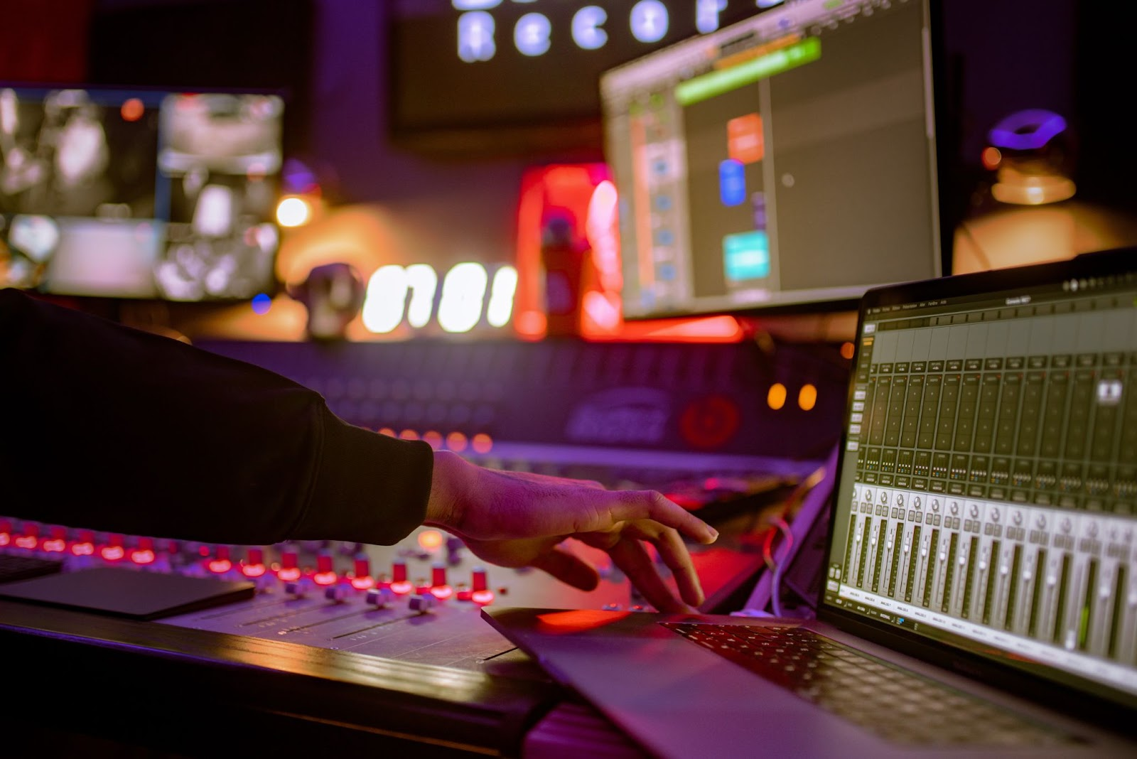 Individual using soundboard and computer to make music