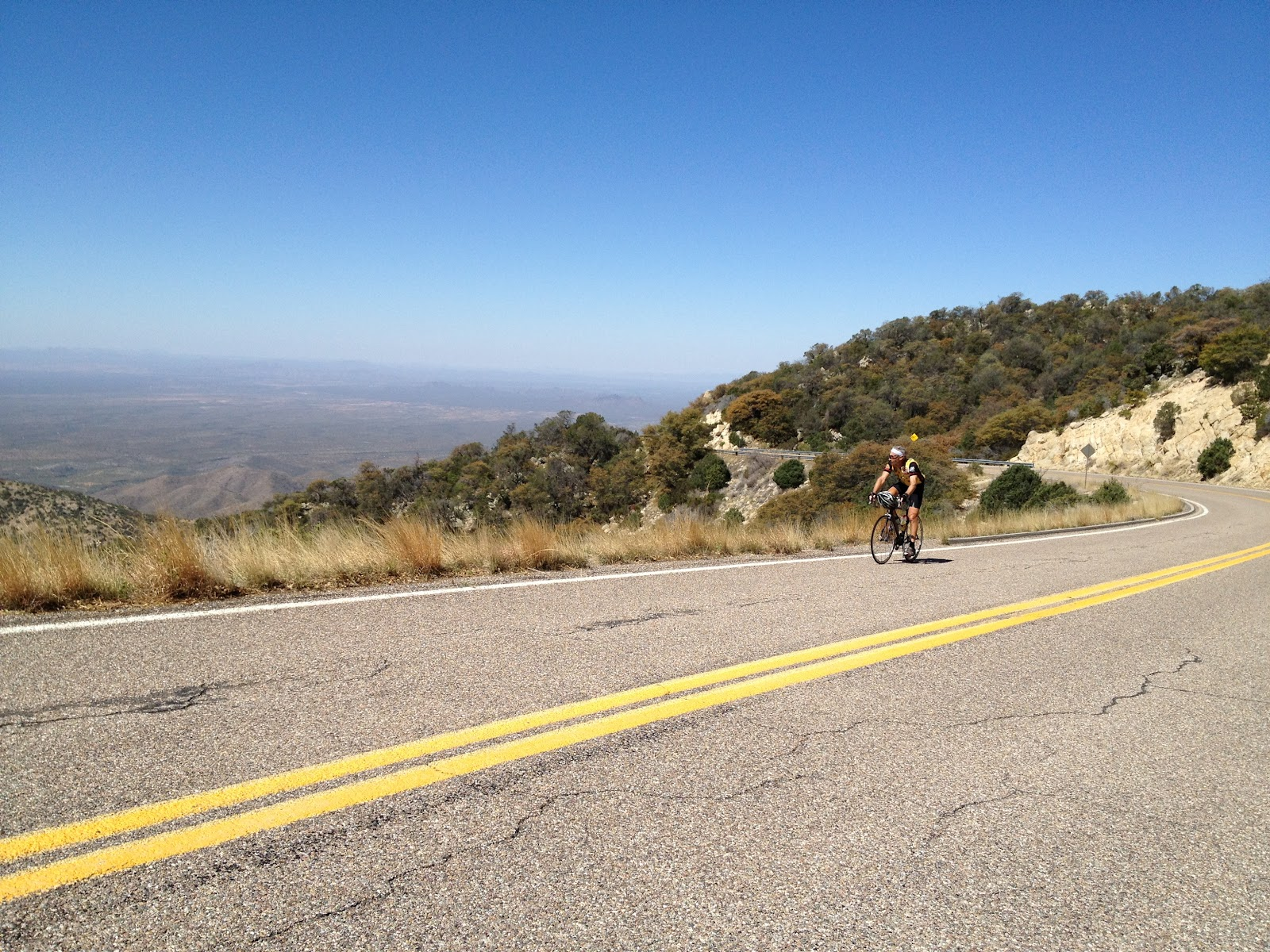 Climbing Kitt Peak by bike - cyclist on road with Sonoran Desert in background