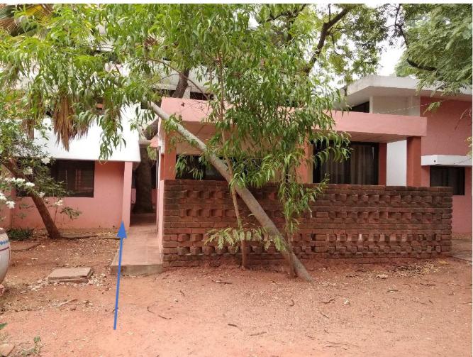 Di sebelah kiri single-based villa yang tertutupi oleh dinding batu bata adalah sebuah ruang transisi dengan pohon yang seakan-akan menghalangi jalan masuk