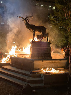 The Elk of Chapman Square on its final night atop its fountain, surrounded by fire and smoke.
