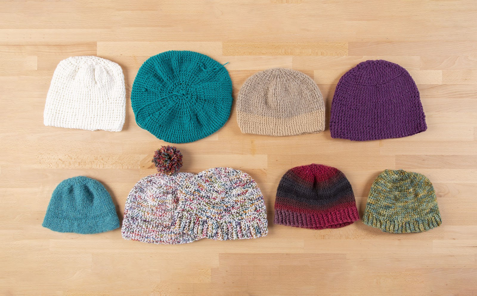 Nine versions of the Brava Beanie hat crochet pattern laying on a table.