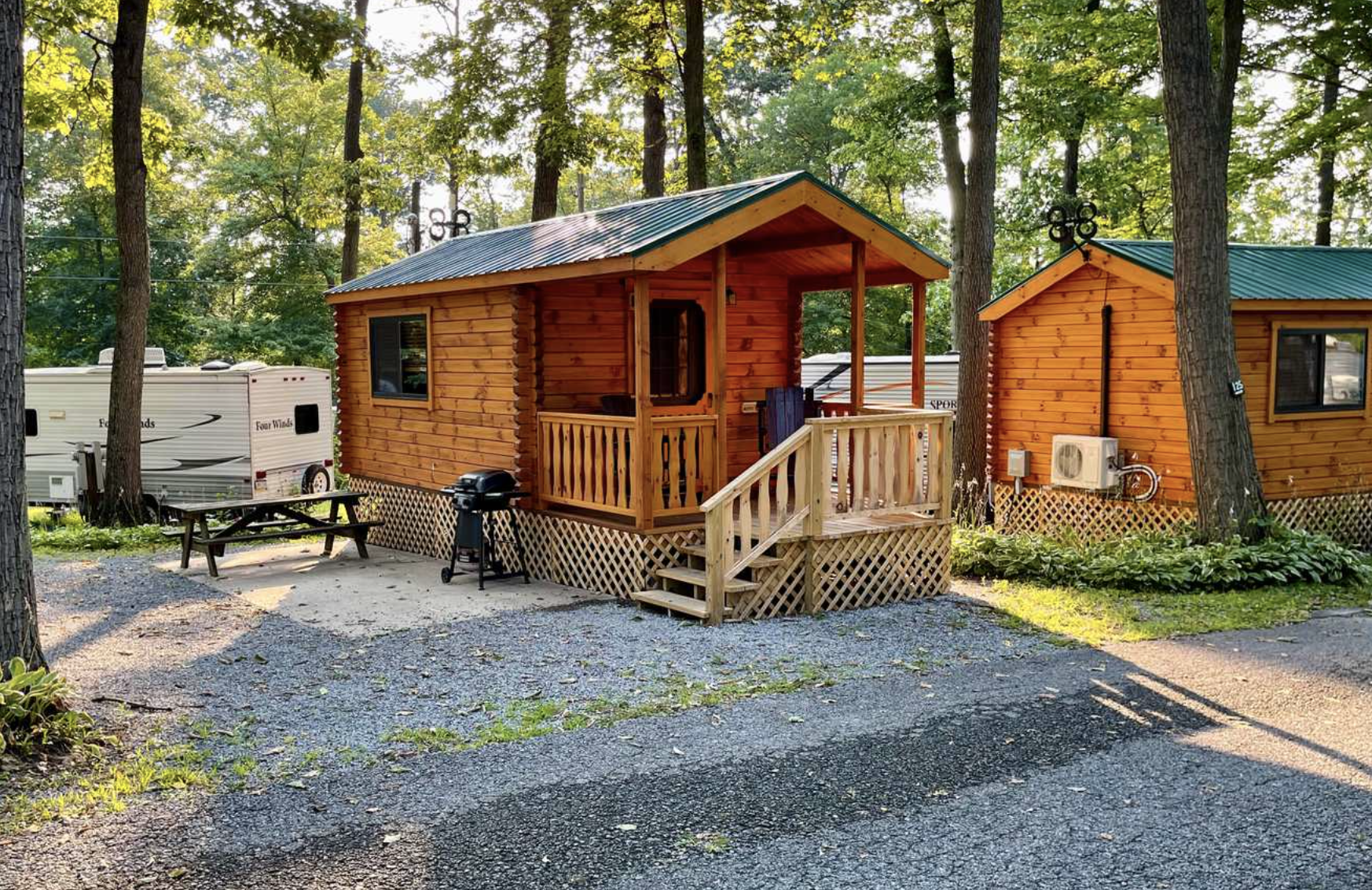 Cabins at campground with trees and RV in the background