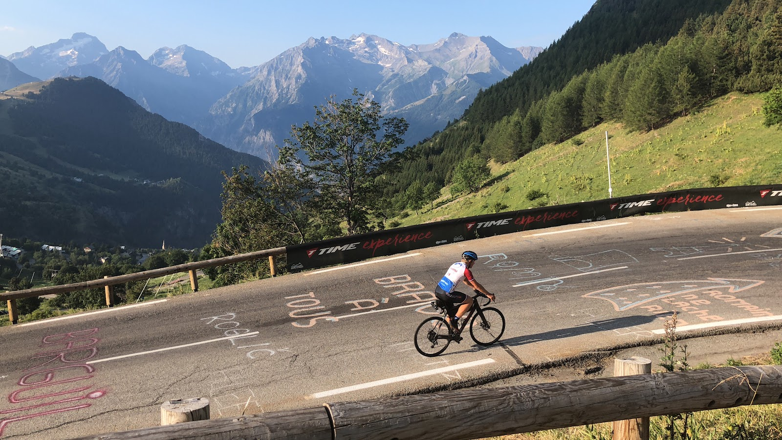 Cycling Alpe d'Huez - cyclist riding bike over road with tour de france road paint, mountains in background