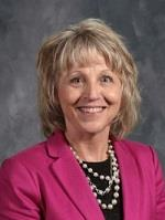 Reading Specialist Jeri Powers smiles for the camera for her school photo.  She has shoulder-length blonde hair, and wears a black blouse and hot-pink jacket, with a necklace of large white beads.