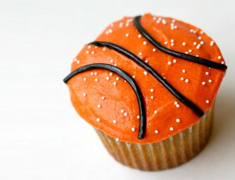 Picture of a cupcake decorated with orange and black frosting to look like a basketball.