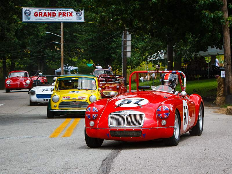 vintage race cars racing in the streets under a Pittsburgh Vintage Grand Prix banner