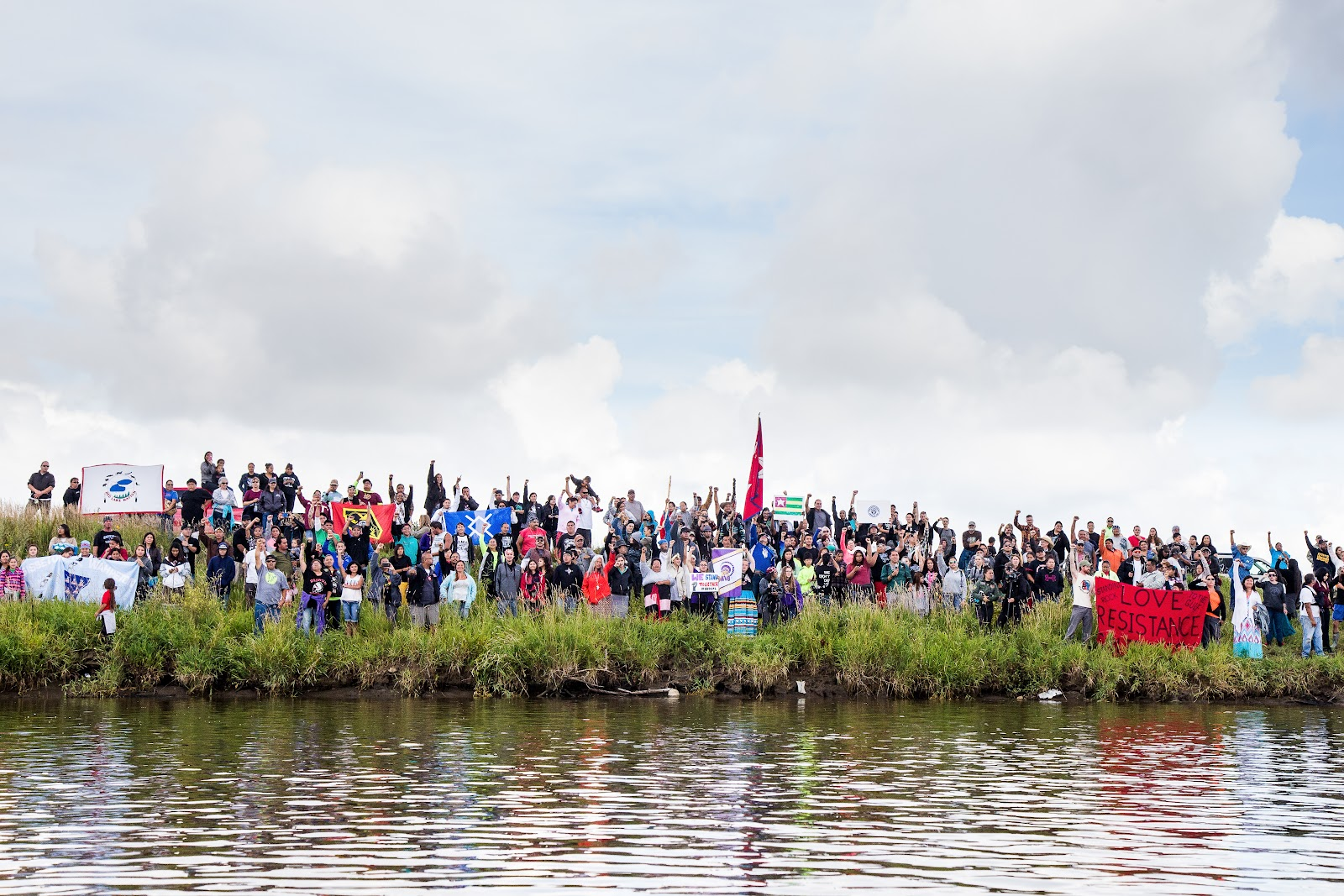 Onkwehone, Real People, stand along the river in support of clean water for all people. (Photo: Alex Hamer)