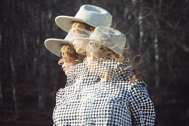 Multiple exposure image of a woman with red hair wearing a white hat and a black and white checkered blouse