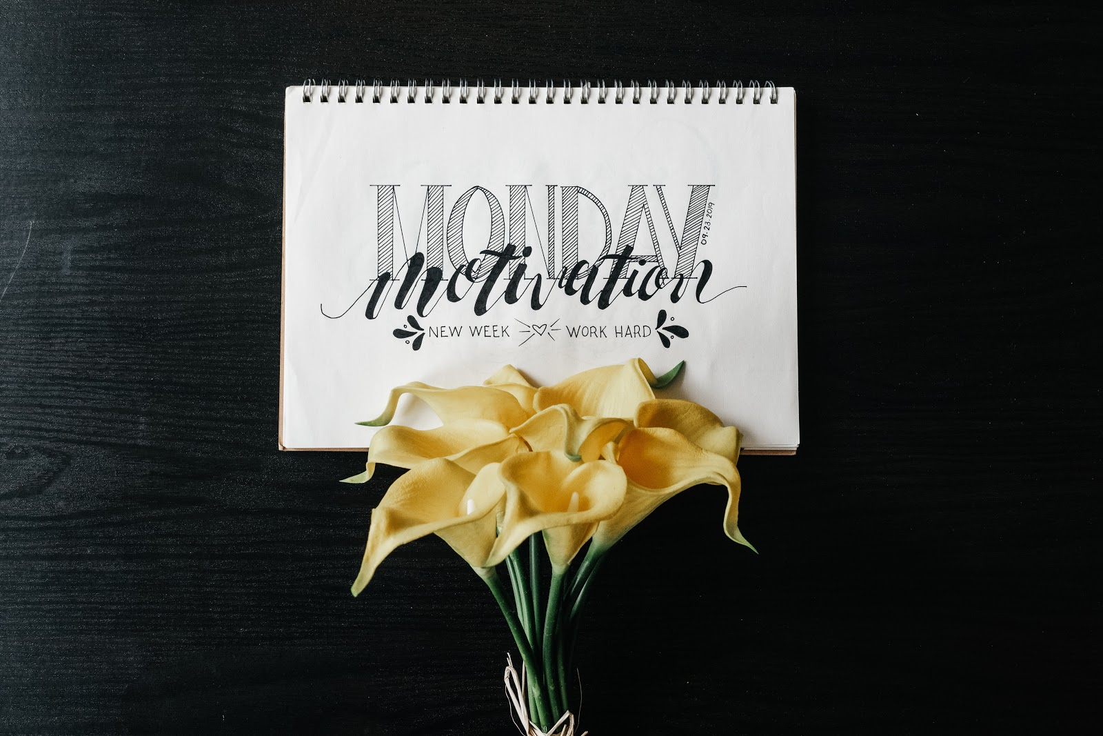 Notebook with written lettering on a black table with flowers