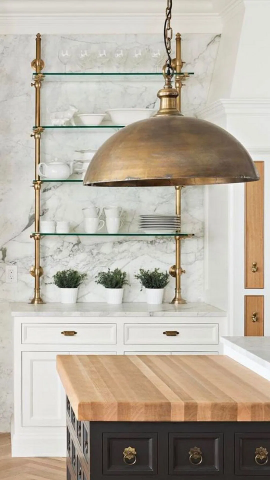 white kitchen design with antique brass pendant light and open shelving for ceramic dishware. a black island with butcher top countertop sits in the middle of the space