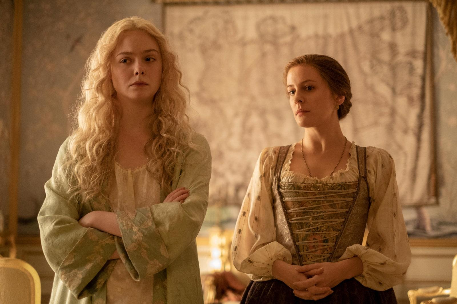 The Great (2020). Catherine has her long blonde hair loose, wearing a white night dress and a pale green robe. She has her arms folded, looking skeptical. Beside her is servant Marial (Phoebe Fox), a shorter white woman with light brown hair tied in a low bun. She wears a cream blouse with a beige floral corset over the top, her hands clasped in front of her. Marial gazes in the same director as Catherine, seemingly more curious than suspicious.