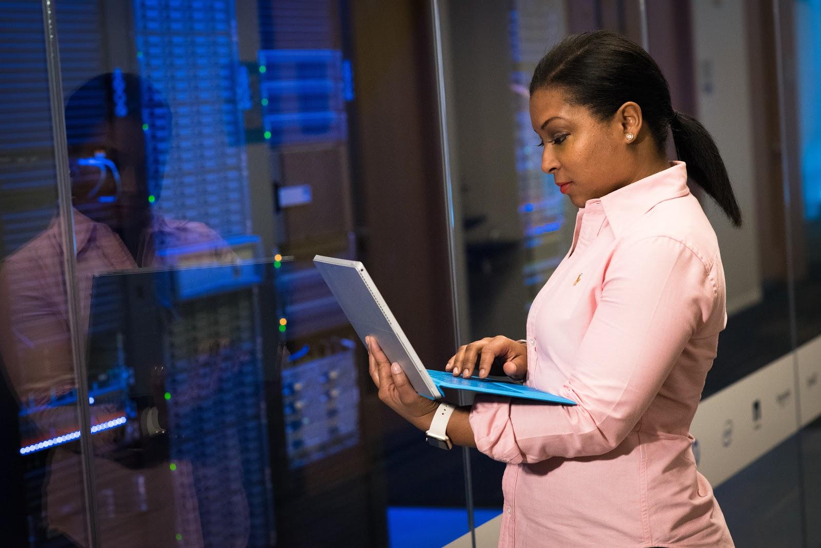 A woman works on a laptop near a server rack