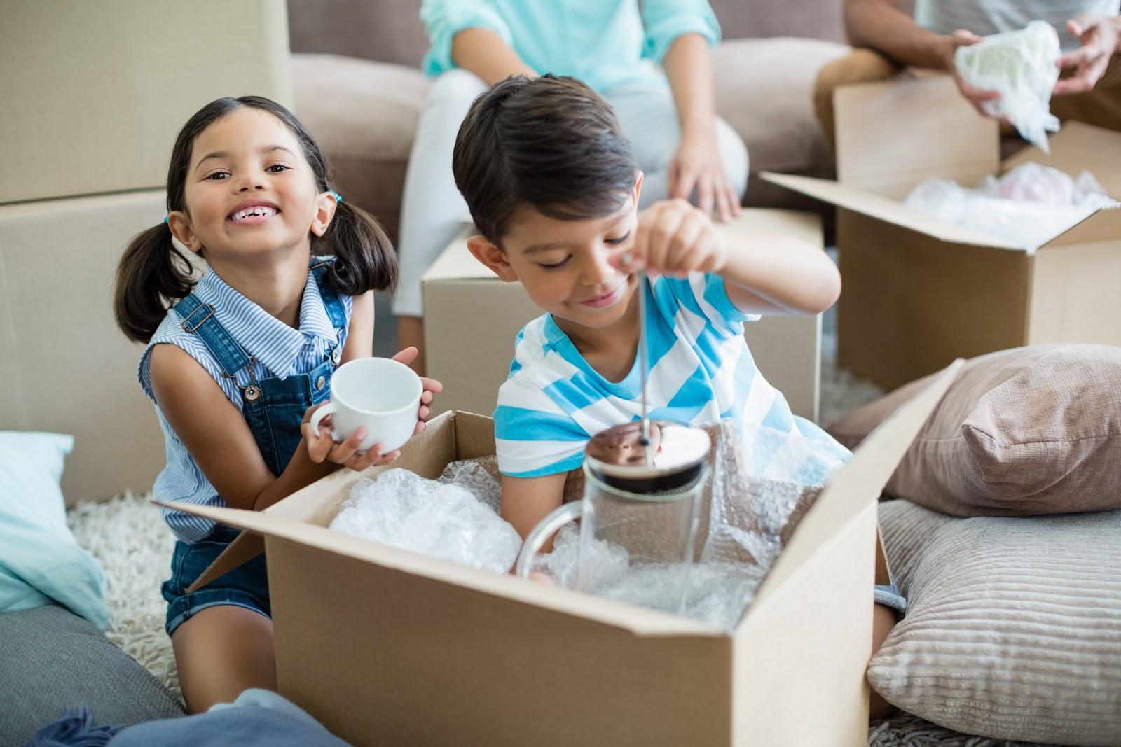 Duas crianças brincando com objetos empacotados em uma caixa.
