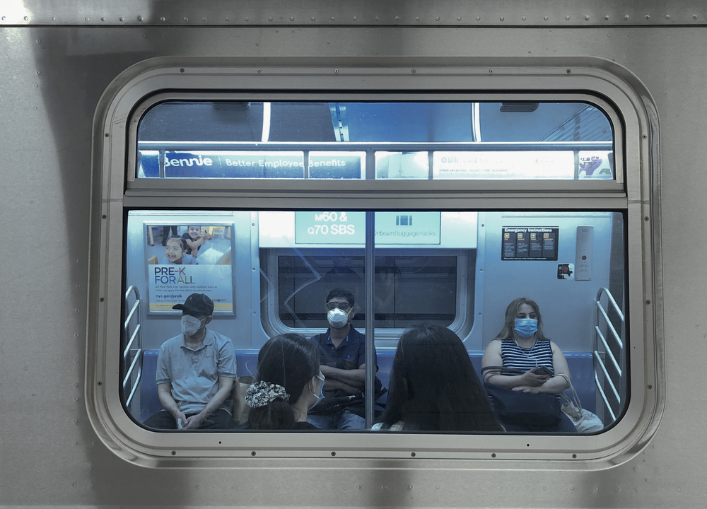 Janela de metrô com pessoas sentadas usando máscara