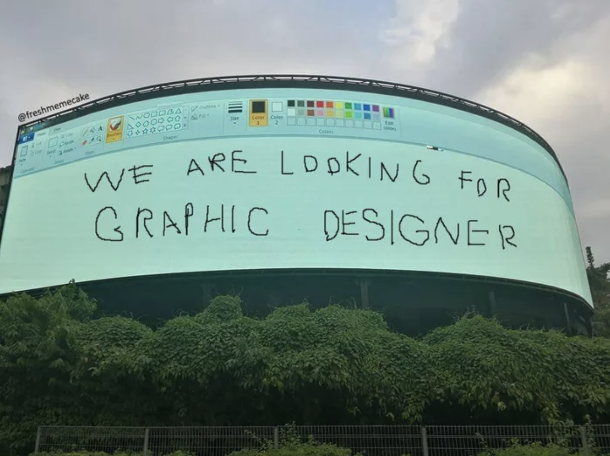 An LED billboard showing a tacky design on paint application looking for a graphic designer.