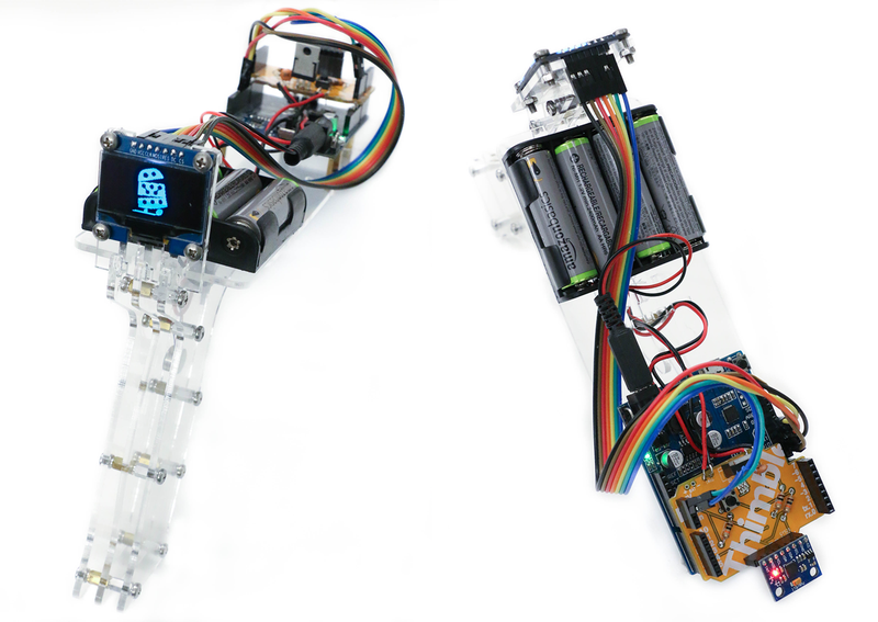 This is an image of Thimble's AI Kit completed. It appears like a clear plastic video game gun with a small screen, battery pack, and multi-colored wiring.