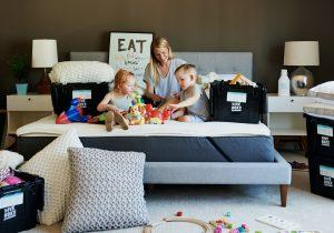 A family of three sitting on the bed, packing