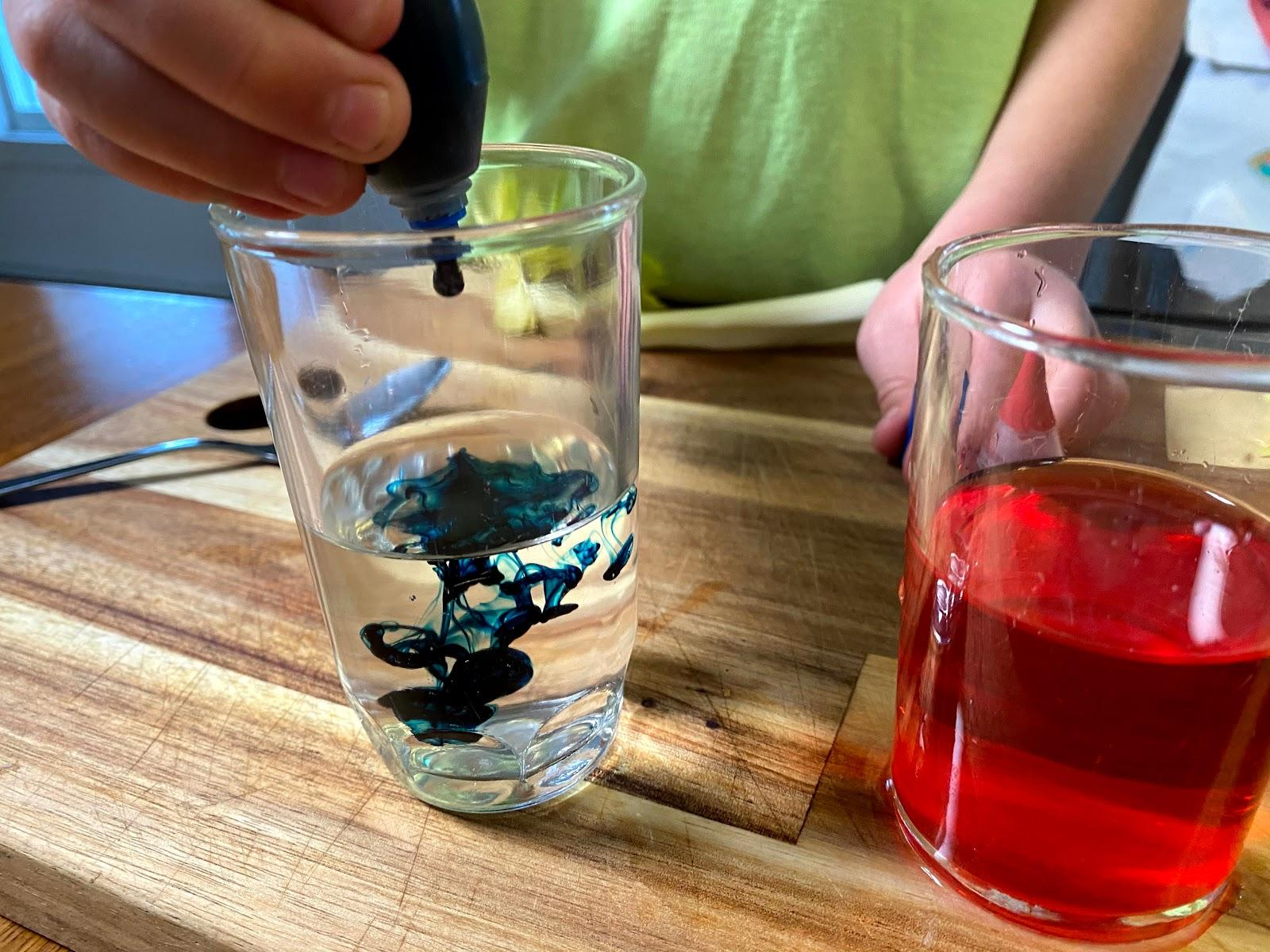 Squeezing drops of blue food coloring into a glass of water.