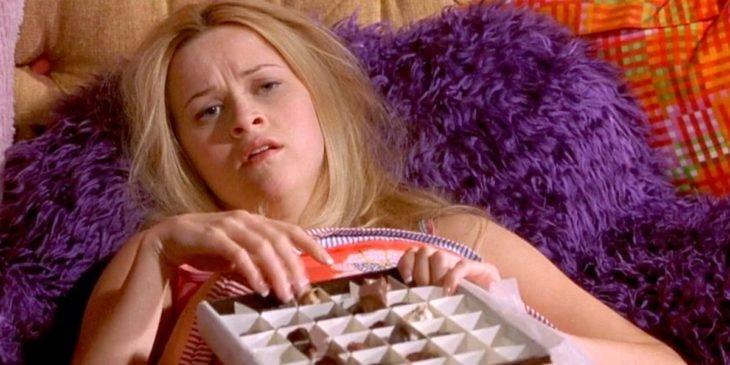 una mujer con cara de enferma comiendo chocolates acostada en la cama