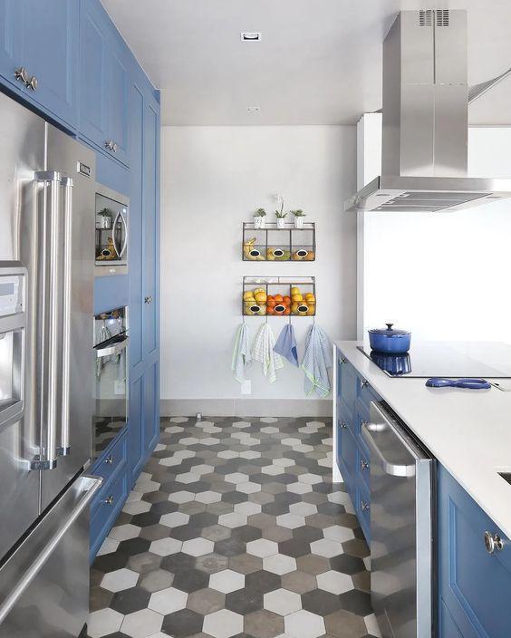 Cozinha com piso hexagonal em tons preto, cinza e branco, armários azuis, bancada da pia branca e eletrodomésticos de inox.