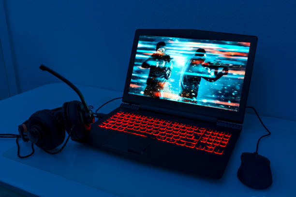 Gaming laptop with connected mouse and headphones Gaming laptop stands on a table. It is night and the keyboard lights up with red colors. A computer mouse is connected and also headphone with a microphone. The screen shows a video game with a soldier firing a rifle. The image on the screen is the photographer's work laptop gaming stock pictures, royalty-free photos & images