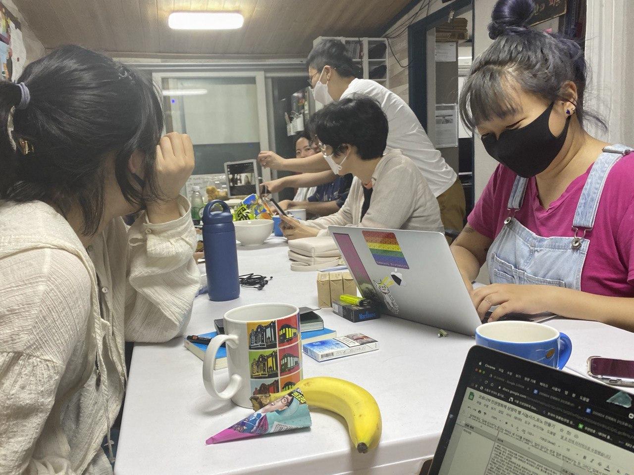 [그림1. 오프라인 참여를 하는 활동가들이 세로로 긴 책상에 모여 앉아있다. 온라인 참여를 하는 활동가들도 있다. 책상 위에는 회의에 필요한 노트북과 화상 회의를 위한 아이패드가 놓여있다. 온라인 참여를 하는 활동가와 오프라인 참여를 하는 활동가가 아이패드로 소통하고 있다.]