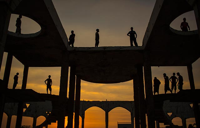 Young men watch the sunset from a destroyed building situated near the Mediterranean Sea in the Gaza Strip, May 29, 2015. (Photo: Wissam Nassar / The New York Times)