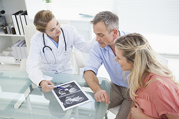Parents looking at an ultrasound with a doctor