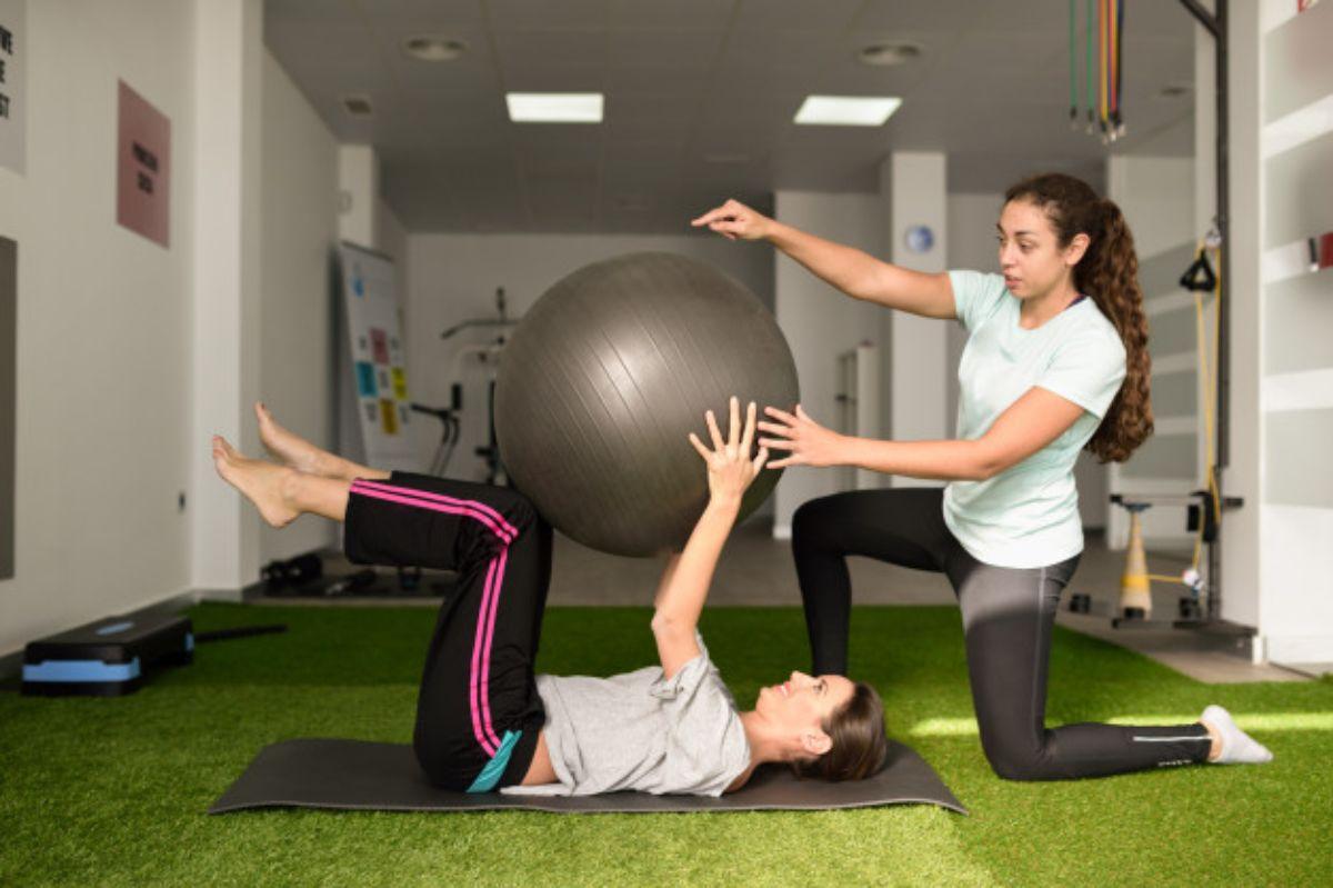 Ejercicios en centro de fisioterapia con balón medicinal como implementos de yoga