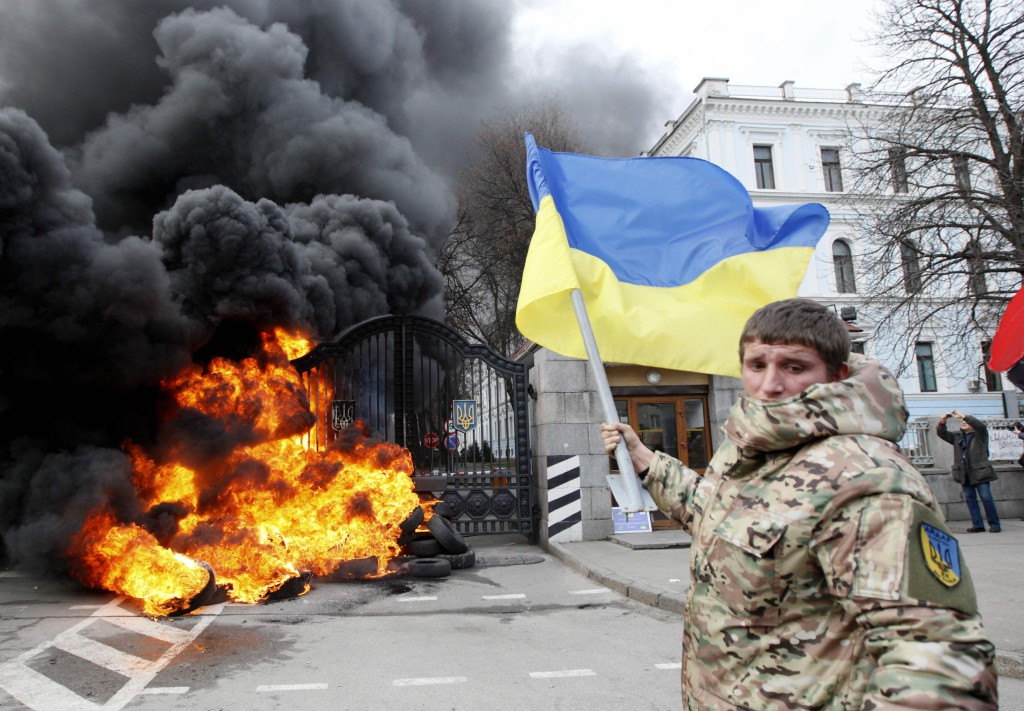 "A serviceman from the battalion ""Aydar"" waves a Ukrainian flag during a protest in front of Ukraine's Defence Ministry in Kiev"