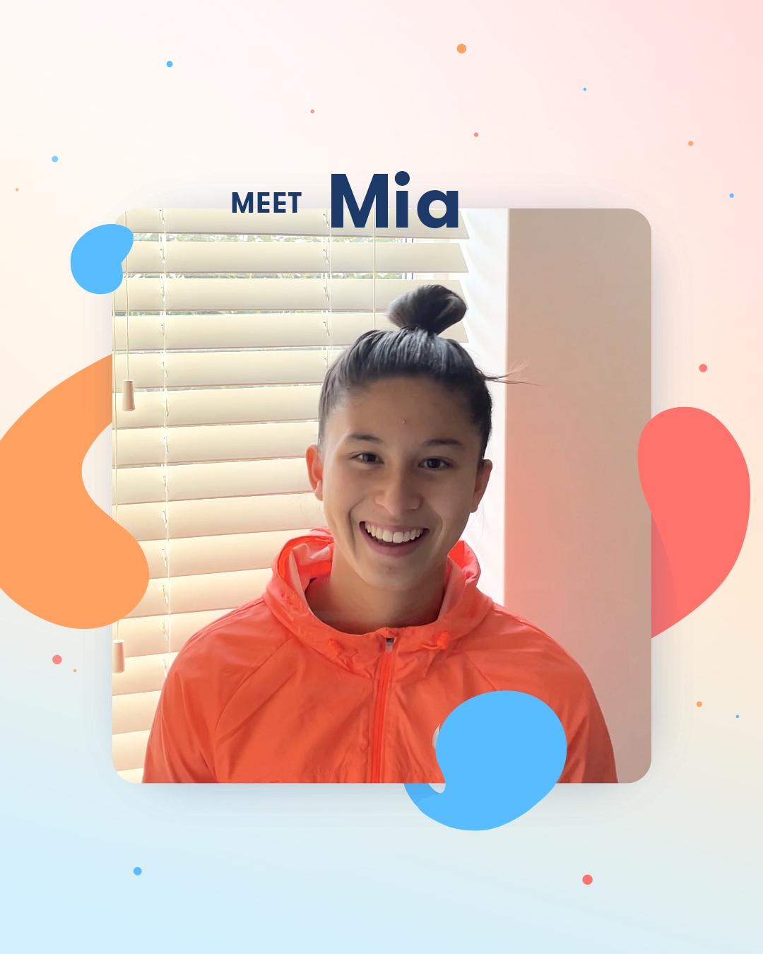 Mia stands with her hair pulled into a tight bun in front of a window, wearing a pink windbreaker.