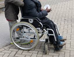 Image of a young man being pushing in a standard manual wheelchair by a friend while out and about.