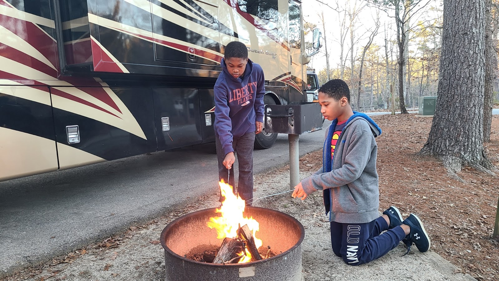 Two brothers roast marshmallows over the fire