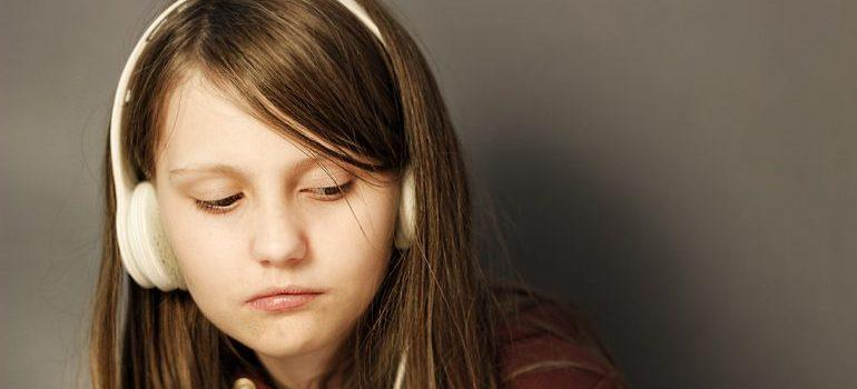 Teenager listening to music to relax because they are moving homes