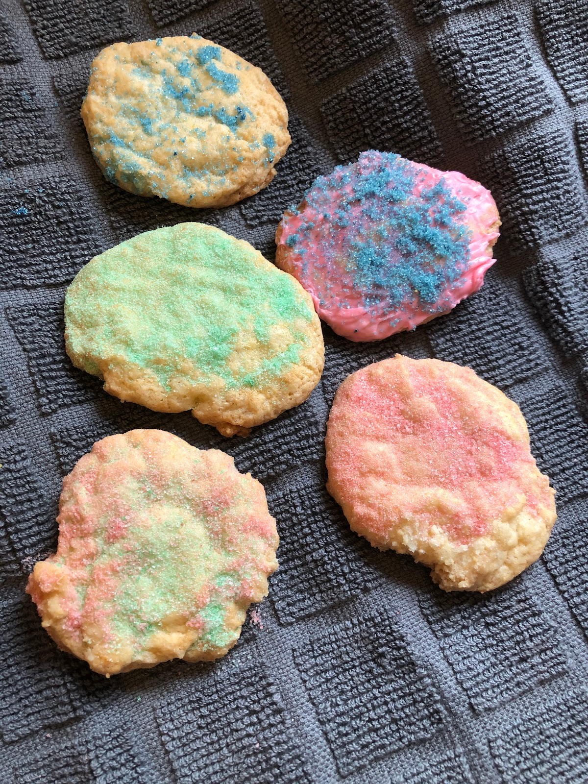 A fresh batch of sprinkle cookies and one frosted ones.
