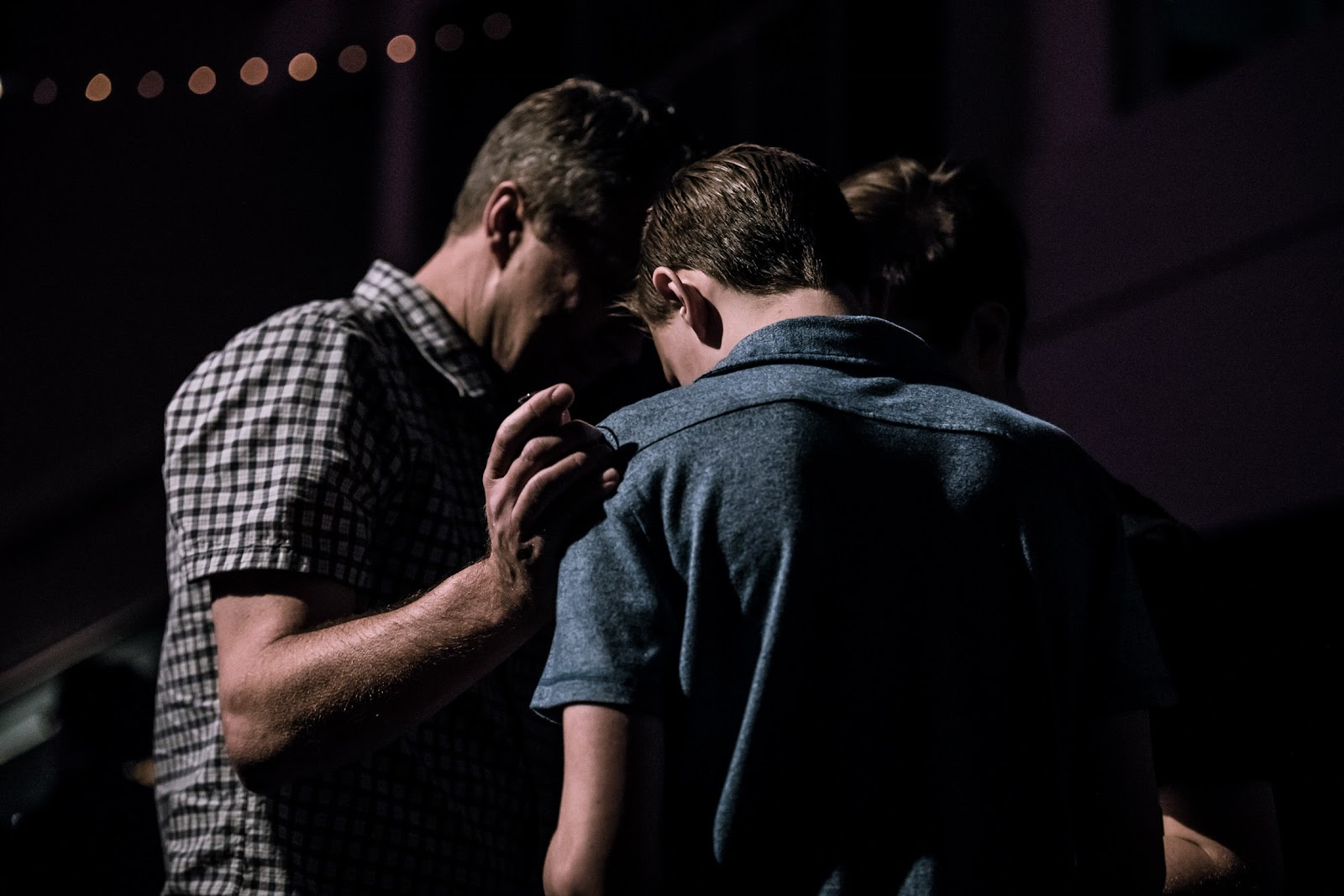 A group of men praying for an unbeliever.