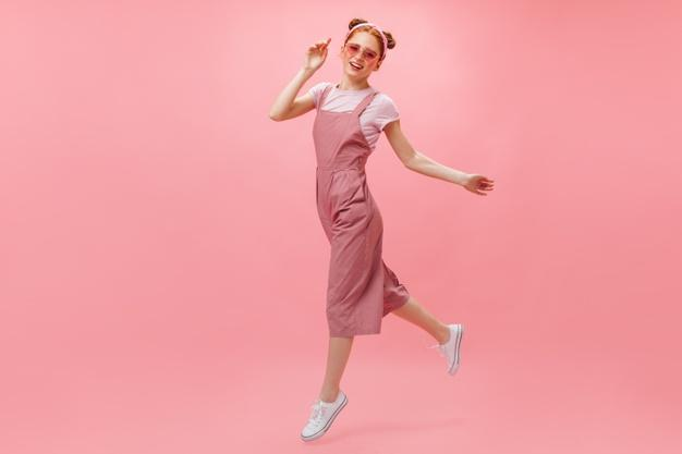 Active woman in pink jumpsuit, t-shirt and stylish glasses moves on pink background. Free Photo
