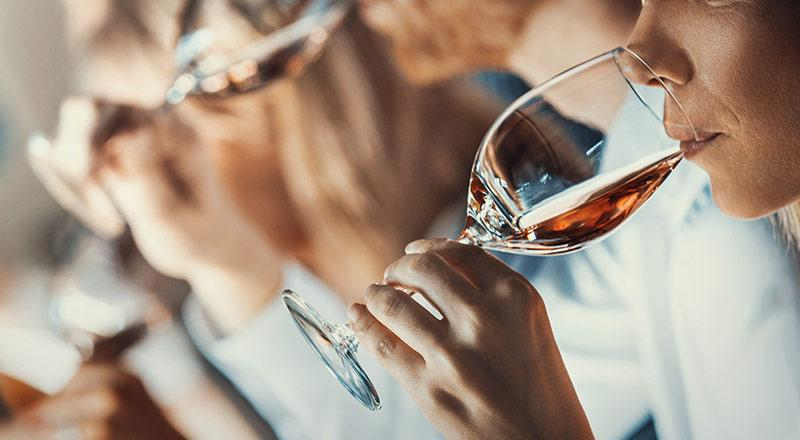 A close up of a person drinking from a glass Description automatically generated