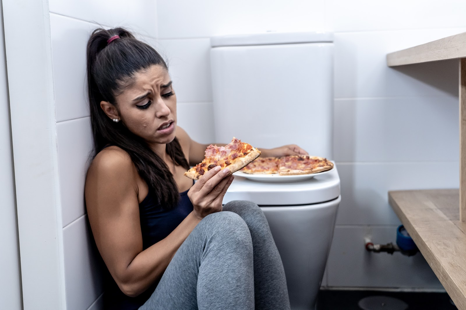 A woman eating a pizza while sitting on the bathroom floor next to the toilet