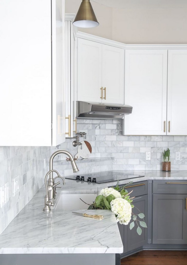grey subway tile backsplash next to matching white marble countertops. White and grey cabinets with gold hardware
