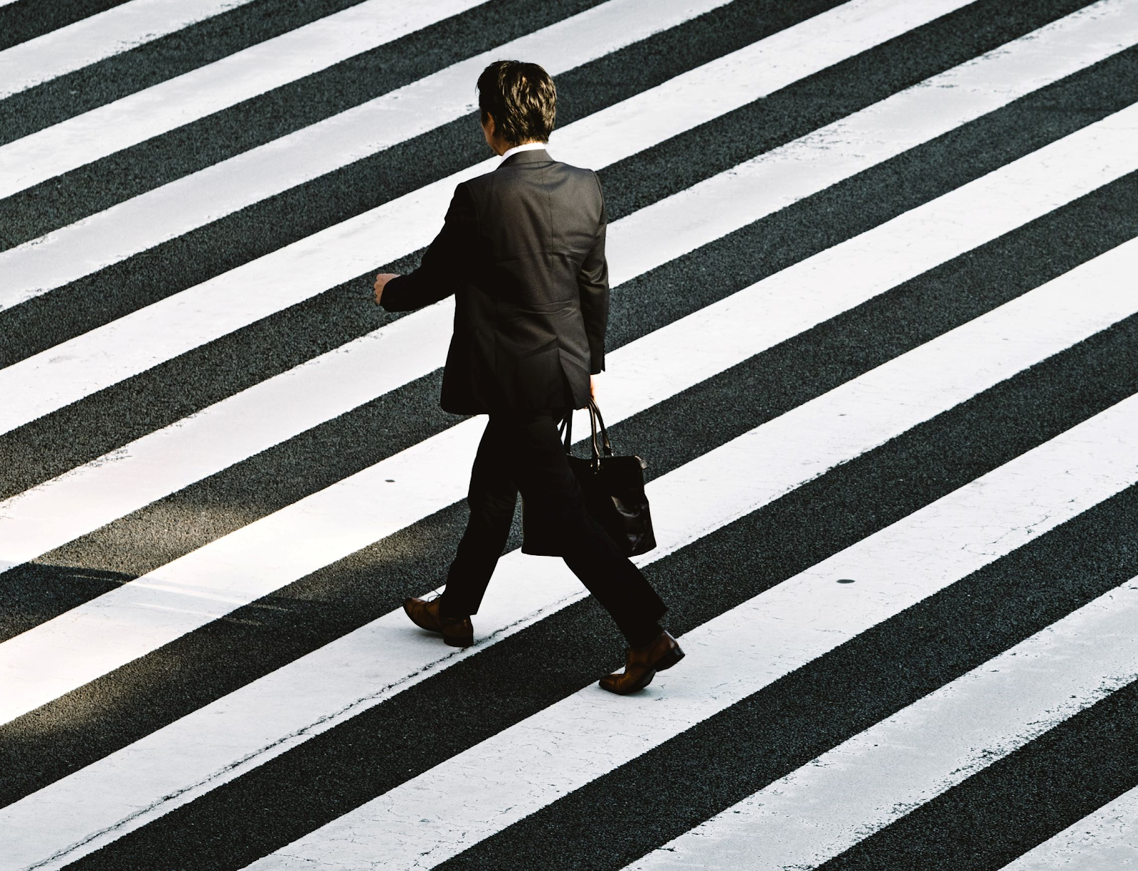 Man in a suit with a briefcase crossing the road en route to a case interview.