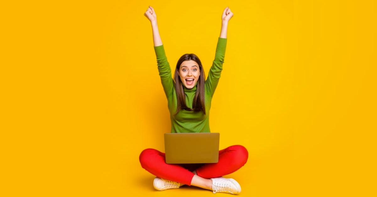 women with laptop celebrating